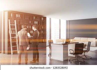 Businessmen in ceo office with gray walls, concrete floor, white and wooden computer table and gray bookcase with folders and ladder. Beige sofa and amrchair near coffee table. Toned image