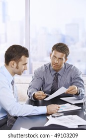 Businessmen discussing business report sitting at meeting table in office.