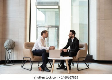 Businessmen discussing deal, sharing startup ideas, business partners negotiations or job interview in modern office with panoramic windows, colleagues talking, working on project together