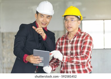 Businessmen discussing on new project, checking a project progress at construction building