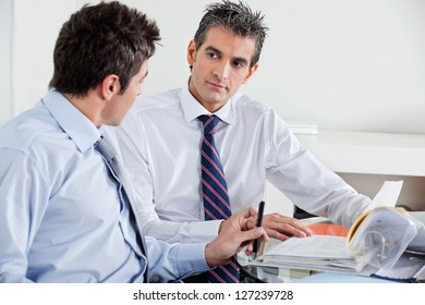 Businessmen discussing paperwork in a meeting at office