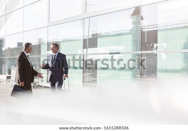 Businessmen discussing plans in the airport