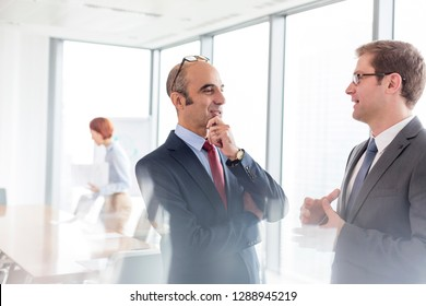 Businessmen discussing while standing in boardroom during meeting at office