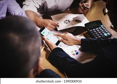 businessmen discussing work sitting in office conference room at night scene, graph analysis and teamwork concept