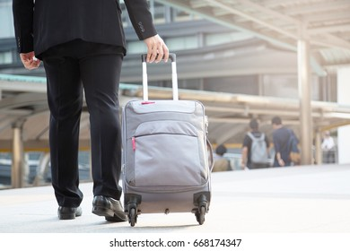 Businessmen drag luggage to head for the airport.