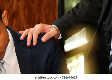 Businessmen encourage : Businessman smashing shoulders encouraging colleagues : Close up of male business man comforting colleagues with worries.