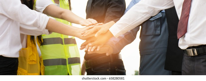 Businessmen and engineers join hands to build successful projects. Teamwork concept.