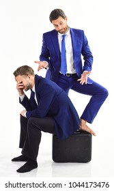Businessmen feel confused and desperate about deal. Unsuccessful exchange or handover. Man or businessman sits on briefcase with desperate expression near colleague, on white background.