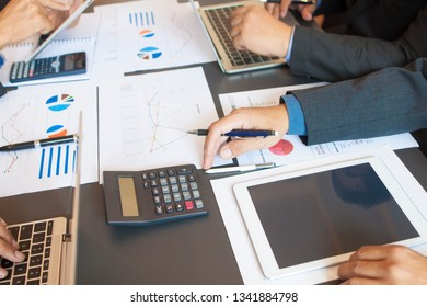 Businessmen and fund managers are meeting to analyze statistics about the profits and financial data of the business. Four fund managers are calculating returns and planning investment strategies.