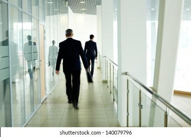 Businessmen going along corridor inside office building