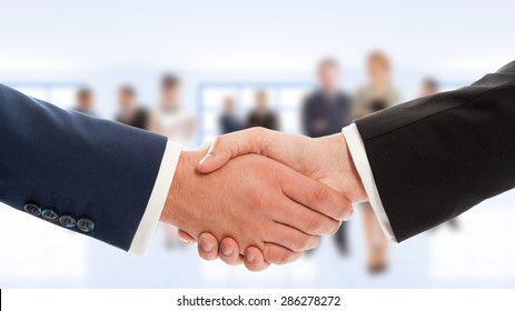 Businessmen hand shake with business people in background. Congratulation or cooperation concept