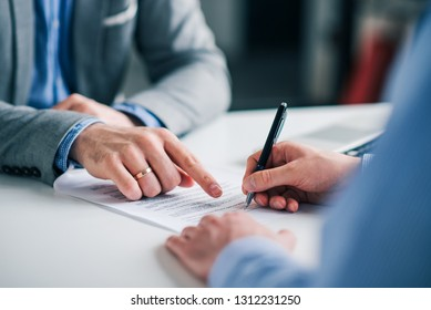 Businessmen hand's pointing where to sign a contract, legal papers or application form.