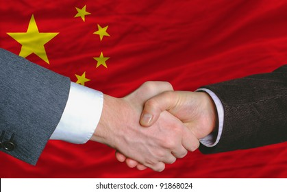 businessmen handshake after good deal in front of china flag