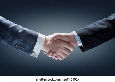Businessmen Handshake. Hands holding on Dark Background