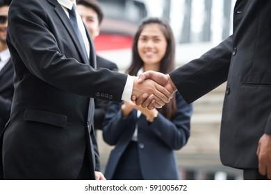 Businessmen handshaking after striking grand deal.