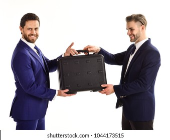 Businessmen with happy faces hold black briefcase. Handover of suitcase in hands of partners on white background. Business exchange between businessmen in classic suits. Business and deal concept.
