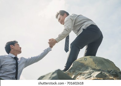 Businessmen with helping hand outstretched for salvation . Strong hold. Teamwork couple helping hand trust in inspiring mountains. Teamwork concept.