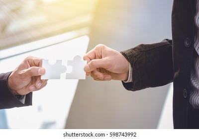 Businessmen hold jigsaw puzzles for each other. Business teamwork concept