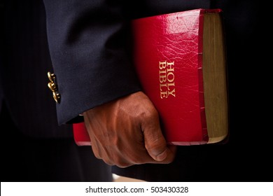 Businessmen holding a Bible.
