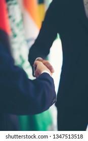Businessmen holding hands With an international flag background