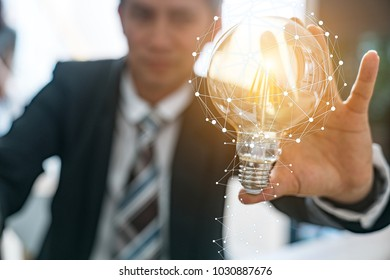 Businessmen holding light bulbs, concepts, ideas, innovations and inspirations.