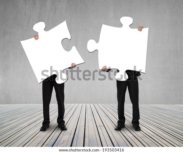 Businessmen holding two puzzles to connect on wooden floor