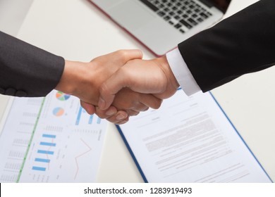 BUsinessmen Join Hands as a sign of cooperation as a Team after Signing a joint venture Agreement.