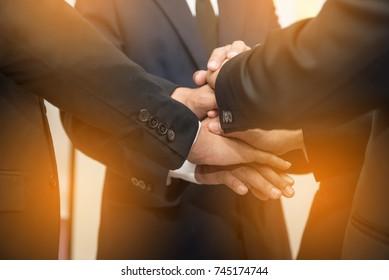 Businessmen join hands together
