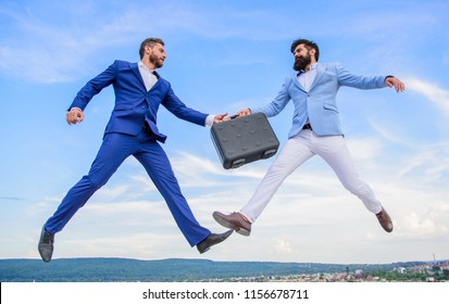 Businessmen jump fly mid air while hold briefcase. Case with raise your business. Successful transaction between businessmen. Briefcase handover in heaven blue sky background. Easy deal business.