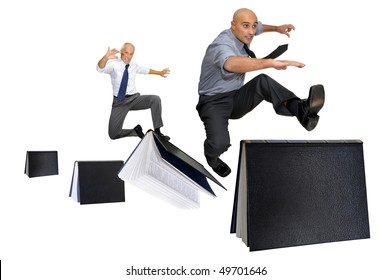 Businessmen jumping over books isolated in white