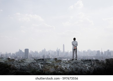 Businessmen look at the city from the outskirts.