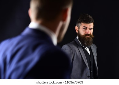 Businessmen look at each other with judgment. Eye contact concept. Business partners on serious faces stand opposite each other. Businessmen, business partners meeting on black background.