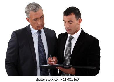 Businessmen looking at a clipboard