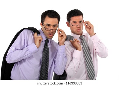 Businessmen looking over their glasses at something