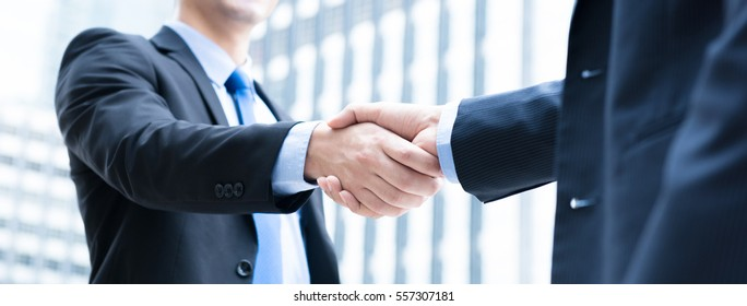 Businessmen making handshake in the city - business etiquette, congratulation, merger and acquisition concepts, panoramic banner