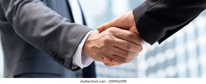Businessmen making handshake in the city for merger and acquisition concept, panoramic banner
