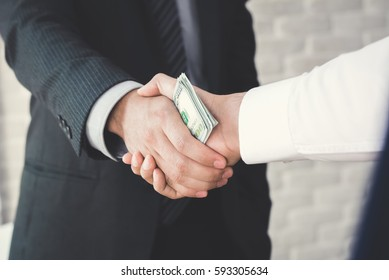 Businessmen making handshake with money in hands - bribery and corruption concepts