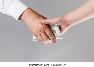Businessmen making a handshake with money in their hands. The concept of corruption, bankruptcy, collateral, crime, bribery, fraud, auction