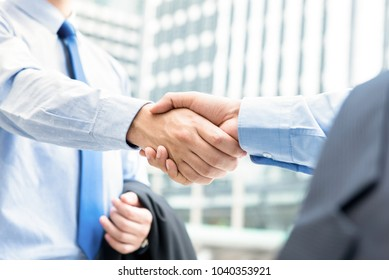 Businessmen making handshake outdoors in front of office buildings in the city - greeting, dealing, merger and acquisition concepts