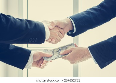 Businessmen making handshake while passing money, dealing & bribery concepts - vintage tone