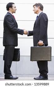 Businessmen meeting outside modern office