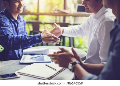 Businessmen negotiate in a coffee shop. Hold hands and greet before the business talks comfortably.