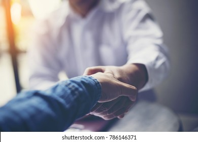Businessmen negotiate in a coffee shop. Hold hands and greet before the business talks comfortably
