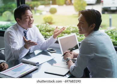 Businessmen negotiate terms and conditions before signing a business co-operation agreement.