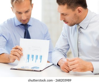 businessmen with notebook discussing graphs on meeting