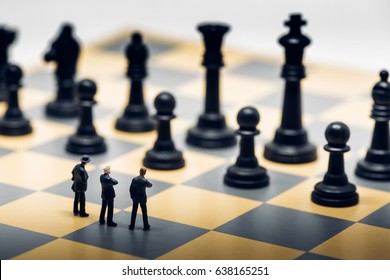 Businessmen on a chessboard. Business strategy concept.