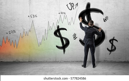 Businessmen on colorful profit chart background placing hands on a wall with black painted dollar signs and hand prints. Business and finance. Oil and gas industry. Investment and banking.