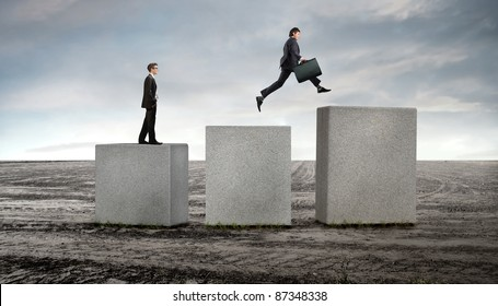 Businessmen on stone cubes advancing on higher ones