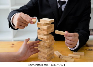 Businessmen picking wood blocks to fill the missing wood blocks and protect wood blocks to fail. Growing business concept.