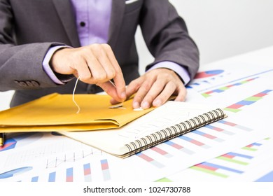 Businessmen are piling documents received from customers for analysis.
